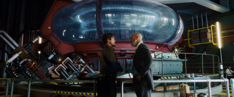 Tony and Obadiah Stane having a conversation in front of the original Arc Reactor at the Stark Industries Headquarters.